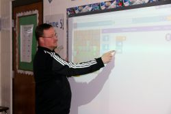 Mr. Krieger conducts a computer science lesson utilizing a smart board.